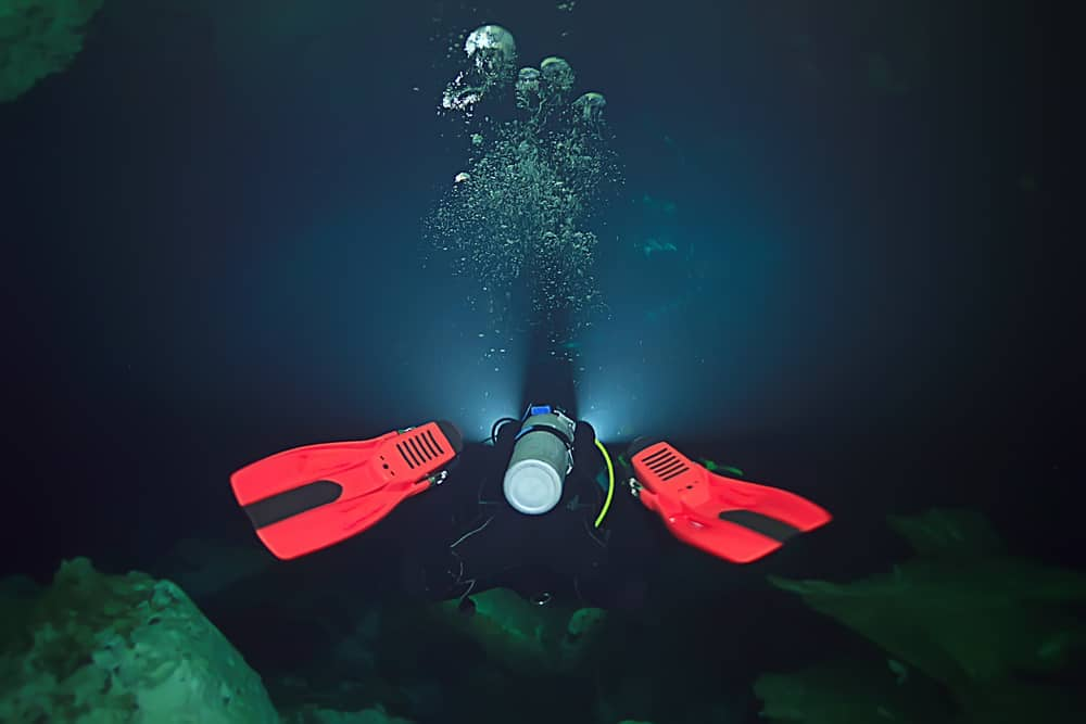 Diver in the dark with bright scuba diving fins