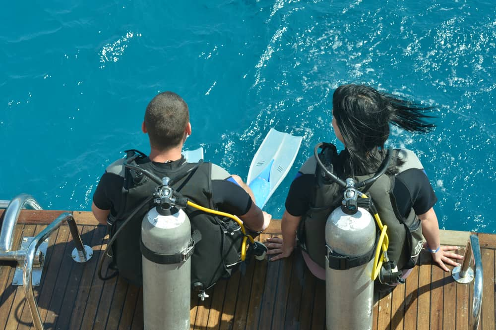 Scuba divers seated for entry into the water