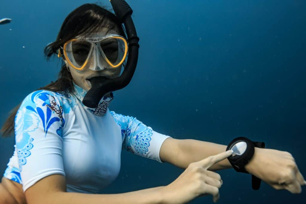 Diver pointing at her working dive computer